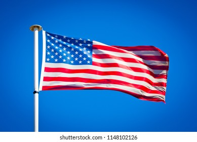 American flag blowing in strong wind against pure blue sky. Stars and stripes, symbol of national patriotism.