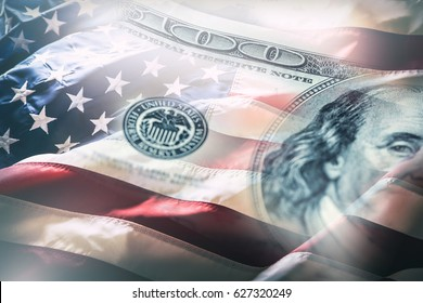 American flag blowing in the  wind and 100 dollars banknotes in the background.