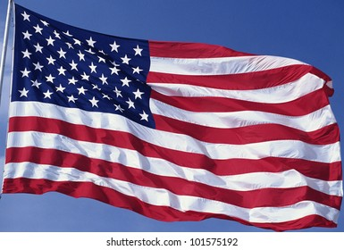 American flag blowing in the wind with a blue sky