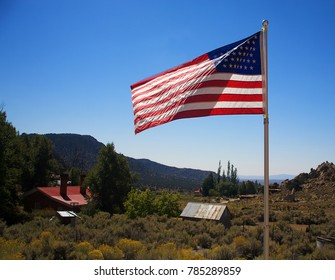 An American flag blowing in the wind with an old town in the background.