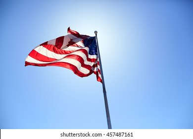 American flag blowing wind on a sunny day on blue sky background.