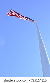 American flag blowing in wind at top of tall flag pole