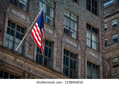 An American flag blowing in the wind while hanging from a building in New York.