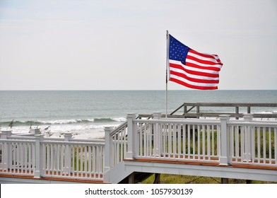 An American flag blows in the wind near the seashore.