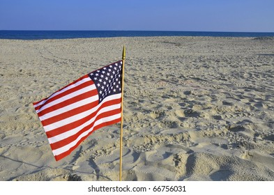 American flag blows in the wind on the beach