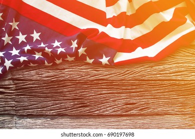 American flag border on wooden background with sunlight