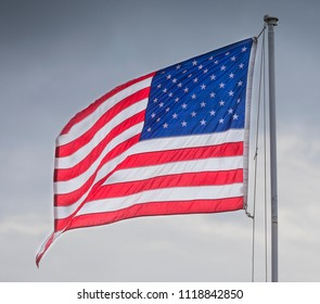 American flag brightly light with clouds behind with motion blur