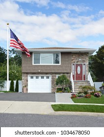 American flag Brown Suburban Split Level Home Landscaped front yard blue sky clouds USA