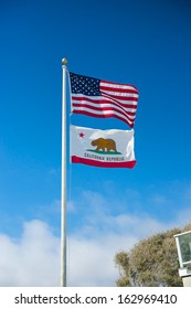 American flag and Californian flag wave in the breeze under a bright blue sky.