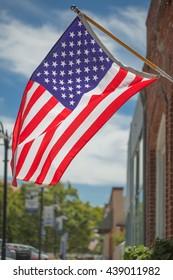 American flag closeup on blue sky background. July 4th celebration.