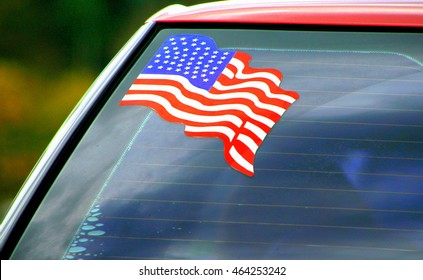 American flag decal on a car windshield outdoors.