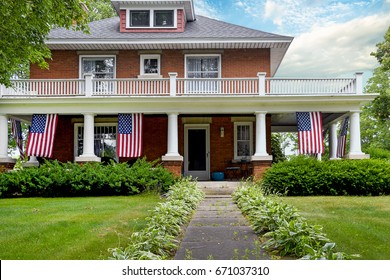 American flag decoration on front porch of old brick home with white columns