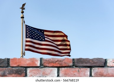 American flag and de-focused brick wall, the United States confrontation and refugees