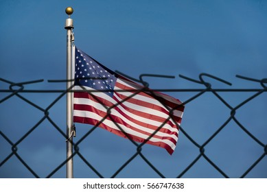 American flag and de-focused fence, the United States confrontation and refugees