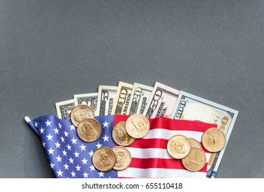 American flag with american dollar bills and coins.