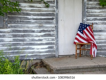 American flag draped over old wooden chair by rustic house door