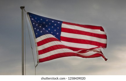 American flag at dusk with a stiff breeze and clouds behind