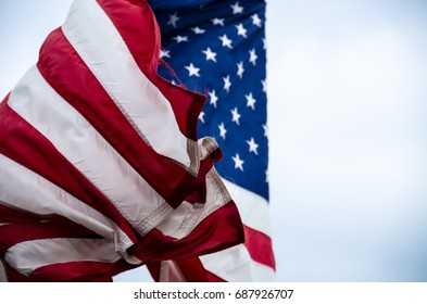 American flag flapping wildly in the wind on overcast day