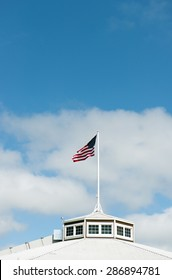 American flag flapping in the wind against sunny sky