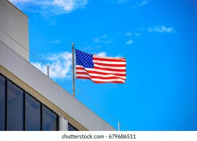 American Flag Flies Against Blue Sky in Bright Sunlight