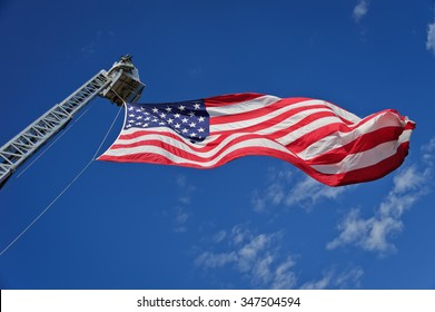American Flag flies from firefighting hydraulic boom. Blue sky above with scattered clouds.