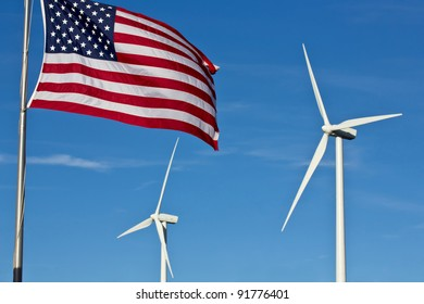 An american flag flies in the foreground, with two wind power generator windmills turn in the background