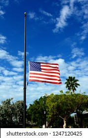 The American Flag flies at half-staff against a deep blue sky with white clouds.