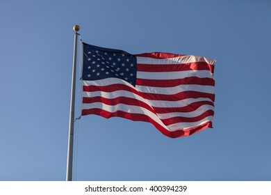 The American flag flies in the wind across a blue sky on Independence Day.