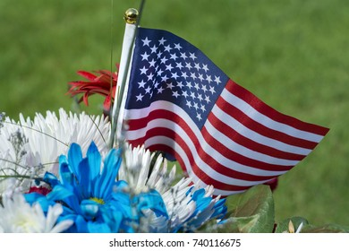 American flag and flowers on grave for memorial day