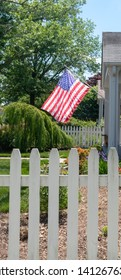 American flag flown in residential neighborhood with white picket fence in foreground.