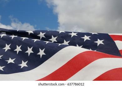American Flag Fluttering in the Breeze in a Sunny Morning against Partly Cloudy Sky