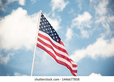 An American flag fluttering in the wind against a blue sky with clouds.
