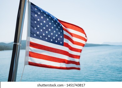 American flag fluttering in the wind on a sailing yacht sailing on the blue sea against the blue sky, the horizon with the shores of the islands.