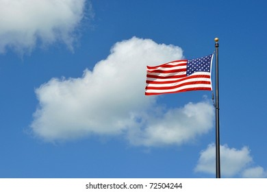 The American Flag Flying Against A Blue Sky With White Clouds On A Windy Day