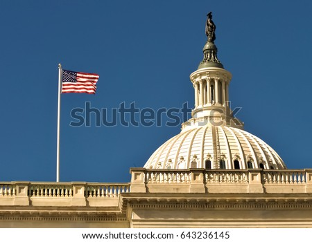 American flag flying with bright blue sky next to capitol dome and freedom statue in Washington, D.C.