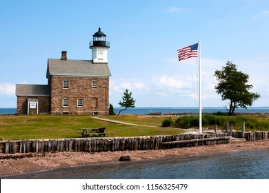 American flag flying near the stone lighthouse of Sheffield Island light in Connecticut on a warm sunny day. It is a popular summertime attraction.