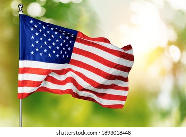 American flag flying on the background of the setting sun in nature.