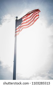 American flag flying on a flagpole blowing in the wind against a blue sky
