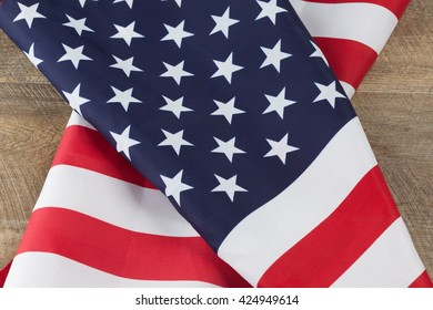 American flag folds on walnut wooden table.