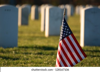American flag in foreground of cemetery grave marker tombstones