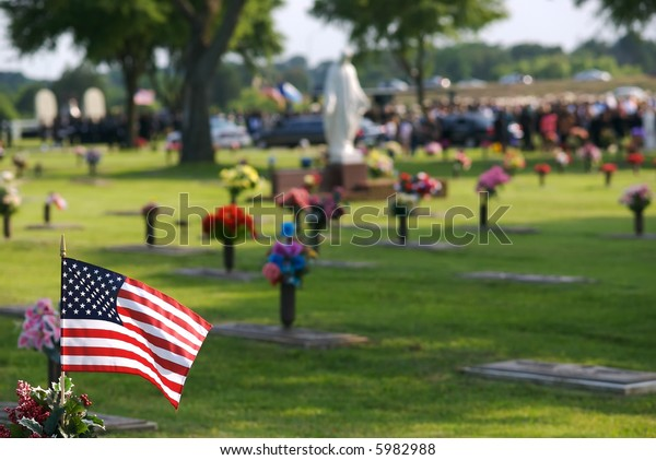 An American flag in the foreground with a funeral taking pace in the distant background.