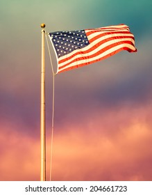 American flag in foreground, waving and brightly lit with rising sun's golden sunlight and ominous clouds in the background, with instagram style retro processing