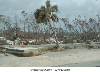 American flag in front of demolished buildings in the aftermath of hurricane Michael in Mexico beach Florida