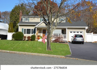 American flag front yard lawn Beautiful Cape Cod Home Autumn clear blue sky day residential neighborhood USA