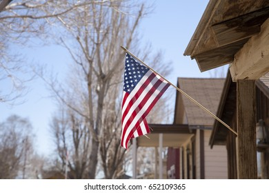 The American flag hanging off a wooden building