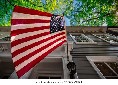 An American flag, hanging on a building in Alexandria, Virginia.