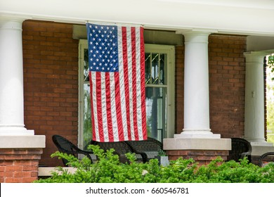 American flag hanging on front porch of old brick house