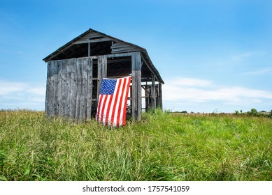 American flag hanging outdoors on side of old gray wooden barn on grass hill in countryside. Pride, patriotism, holidays, symbol, icon, independent, heartland, corn belt, farmers, country, vote, voter