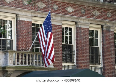American flag hangs above the doorway to a traditional style urban building. Patriotic support