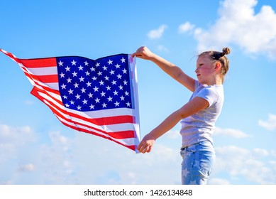 American flag. Happy little patriotic girl holding USA flag waving on blue sky background. National 4 july. Memorial day